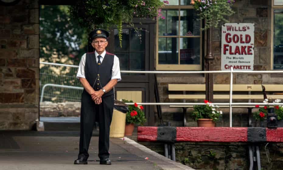 Guard stands on the station of Bodmin and Wenford Railway, Cornwall, UK.