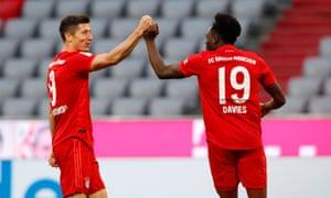Alphonso Davies of FC Bayern Muenchen (R) celebrates after scoring his team's fifth goal with team mate Robert Lewandowski.
