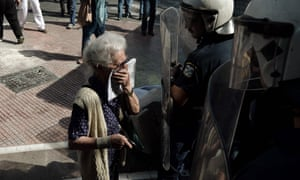 A woman stands in front of riot police after they used pepper spray during a demonstration in Athens