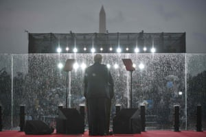 """Donald Trump speaks during the """"Salute to America"""" behind what appears to be bullet proof glass"""