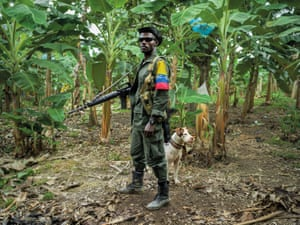 The FARC guerilla fighter Over and the dog Killer pose for a portrait while standing guard. In the past, he would sometimes be fighting every day for half a year. At other times three months could go by without a shot being fired. As part of the peace process, soldiers like Over have moved into UN-controlled areas known as 'normalisation zones' where former soldiers stay in camps to receive training to prepare them for civilian life. The peace process is far behind schedule, houses that should have been ready months ago are still under construction, so former fighters are still living in tents
