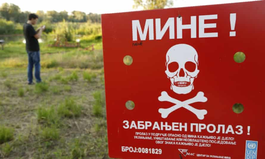 Bosnian man ignores a sign warning of a minefield as he plays Pokémon Go.