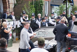 May leaves St Clement's church in London as angry Grenfell Tower protesters surround her car in June 2017