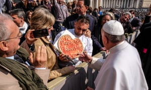 Pope Francis is offered a specially decorated pizza.