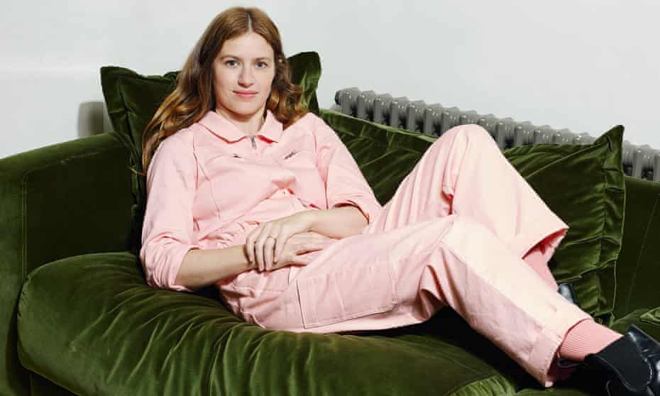 Louise Markey, Founder of LF Markey, photographed on a velvet green sofa in her home in a pink junpsuit.