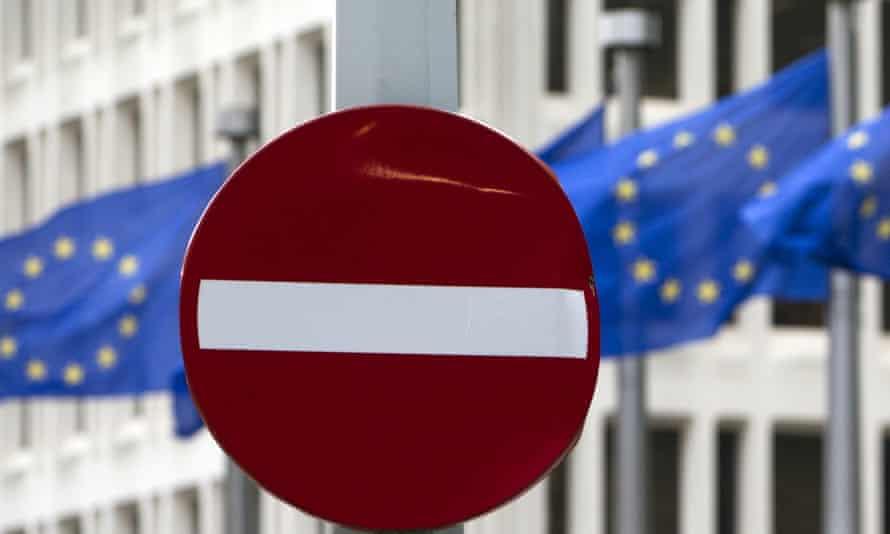 EU flags flutter behind a no entry street sign
