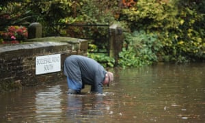 Man unblocking a drain on a flooded road in Whirlow, Sheffield.