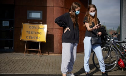 A photograph of students from the same household queueing outside a temporary Covid-19 testing centre near the University of Manchester and Manchester Metropolitan University.