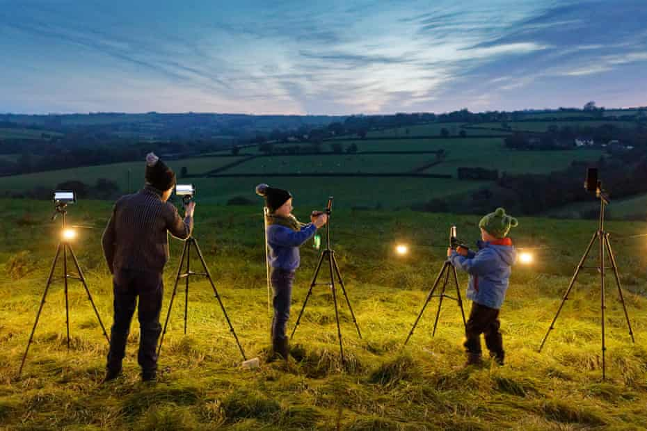 Children photograph the sky after sunset.
