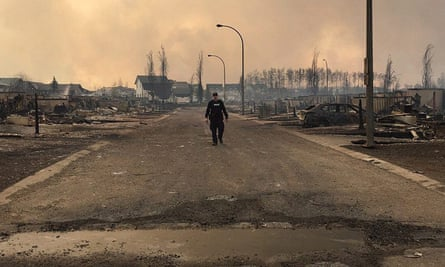 An RCMP officer surveys the damage on a street in fire-ravaged Fort McMurray, Alberta