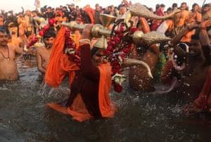 A sadhus, or holy woman, takes a ritualistic dip.