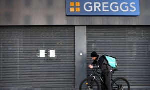 A Deliveroo food courier stands outside a shuttered Greggs shop in Leicester.