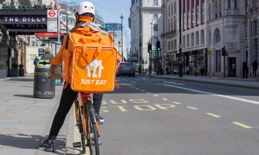 A person stopped by the side of the road on a bike carrying an orange-coloured Just Eat food delivery bag