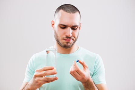 picture of a young man taking a pill