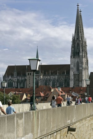 People cross a bridge across river Danube, in front of the Regensburg cathedral.