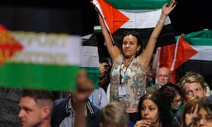 Palestinian supporters wave Palestinian flags during a debate at the Labour conference.