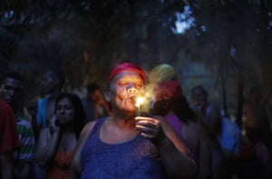 A woman lights a cigar to ask for permission to perform spiritual rituals