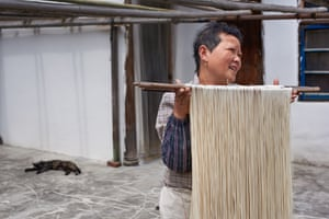 Zhihu Fu, 56, the town's noodle maker in the courtyard of her family's historic home, China