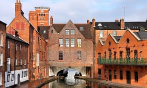A river view of red-brick buildings in Birmingham.