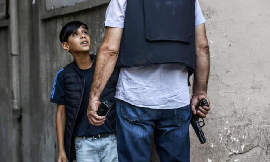 A Turkish policeman questions to a Kurdish boy in Diyarbakir.