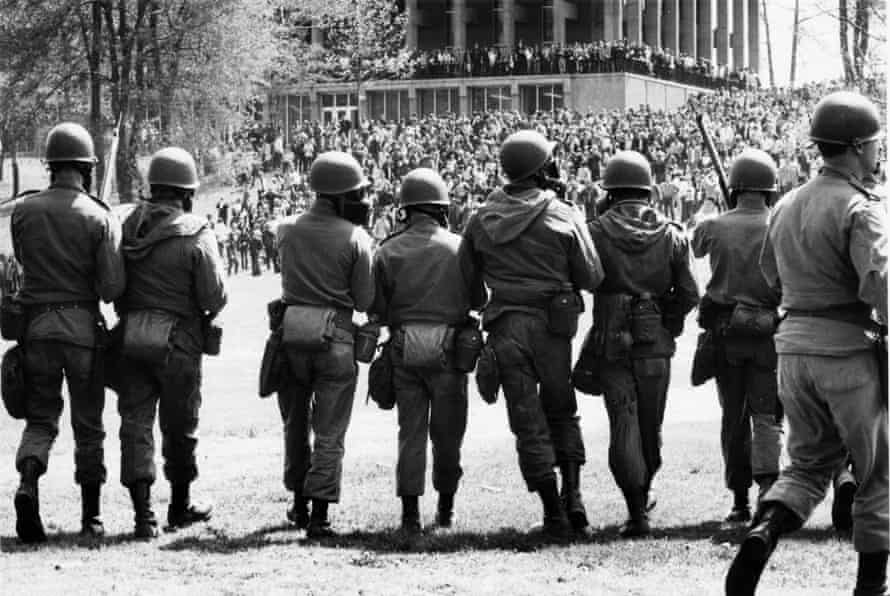 National Guard troops march on pacifist protesters at Kent State University on May 4, 1970;  four students died.
