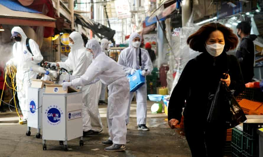 A woman wearing a mask walks past disinfection company workers in Seoul, South Korea