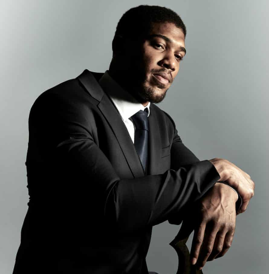 Anthony Joshua sitting on a seat wearing a black suit