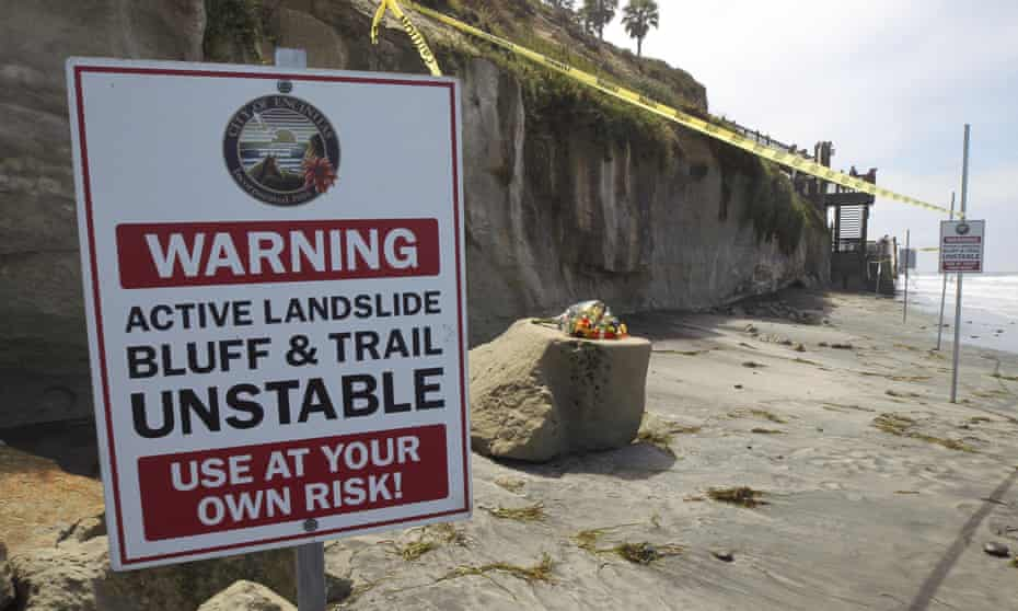 One of several warning signs is posted next to the sand rock debris left from a sea cliff collapse that killed three people.