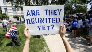 A protester outside the Marshall County Courthouse in Marshalltown, Iowa has a simple question.