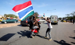 People hold Gambian flags along a street as they prepare for Adama Barrow's return.