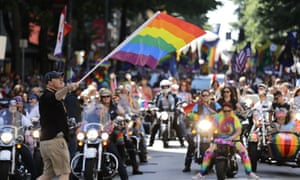 A parade marshal uses a rainbow flag to start the Dykes That Ride in leading the 45th annual Seattle Pride parade.