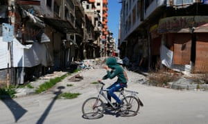A Syrian boy rides a bicycle through  Homs