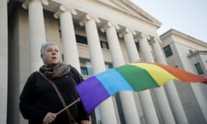 A protester holds a rainbow flag during a rally outside the Alabama supreme court against Justice Roy Moore's opposition to same-sex marriage, January 2016.