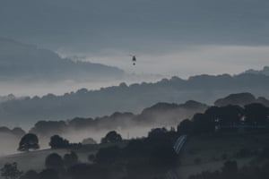 Mist is seen in the valleys before sunrise as a Chinook helicopter prepares to drop sandbags onto the dam wall at Toddbrook reservoir following a severe structural failure after heavy rain in Whaley Bridge.