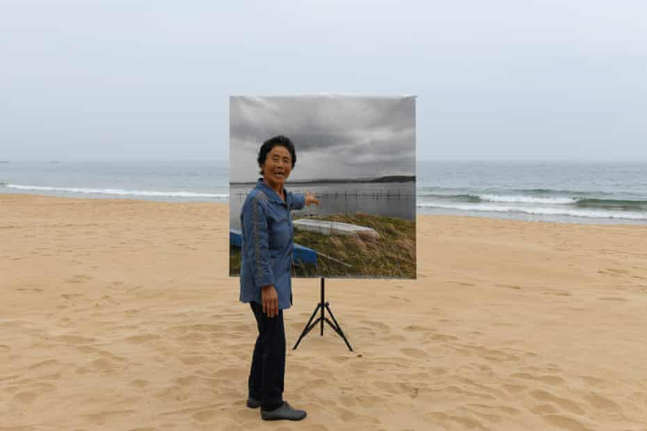 """Akiko looks at the print of her hometown of Ishikawa Prefecture, JAPAN. Since Akiko moved to North Korea in 1967, she hasn't been able to visit Japan. """"The sea was 200 meters away from my home, and oysters cultivated there were sent to Tokyo and Osaka. When the summer was hot, I often went swimming in the sea. I once caught a small octopus with a bait of chili and green onions..."""" Akiko said."""