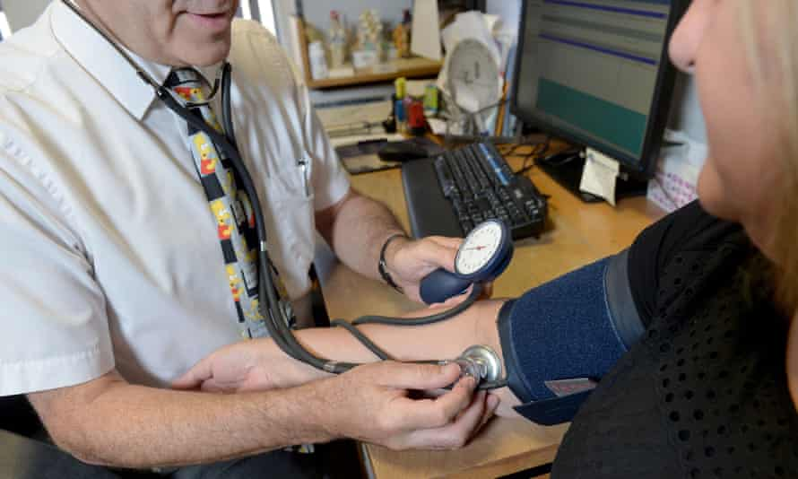 male GP taking blood pressure of female, middle-aged patient