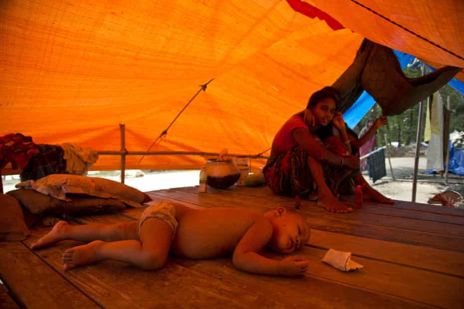 A family takes shelter in a roadside tent in Morigaon district, Assam, India