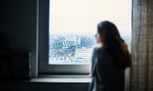 A woman looks out a window.