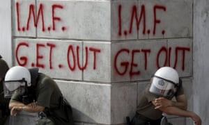 Greek riot police rest in front of anti-IMF graffiti during 2010 protests in Athens over austerity measures