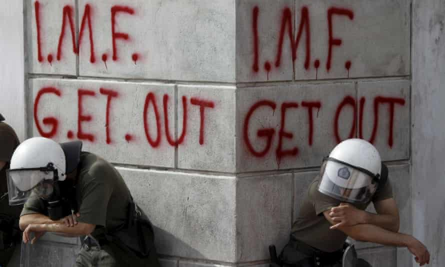 Greek riot policemen resting in front of graffiti reading 'IMF get out'