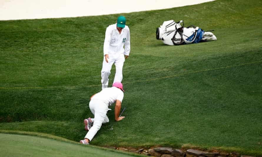 Brooks Koepka is helped out of the creek by his caddy, Ricky Elliott, on the 13th hole.