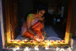 A woman places earthen lamps, or diyas, on the threshold of her home on the eve of Diwali in Hyderabad, India