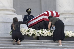 Two women water the flowers near the flag-draped casket on Tuesday.