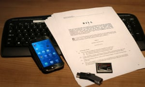 A draft of the investigatory powers bill lies on a laptop beside a phone and a USB stick