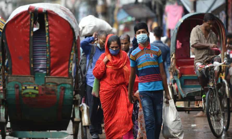 People wearing face masks on a street in Dhaka, Bangladesh.