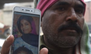 Muhammad Riaz shows a photo of his daughter, 16-year-old Uzma Bibi, who was allegedly tortured and murdered by her employer in Lahore