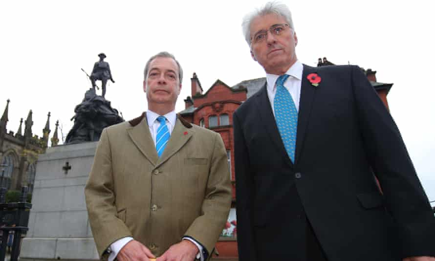 Nigel Farage and Ukip candidate John Bickley, both wearing poppies and looking stern, pose in front of  Oldham's war memorial