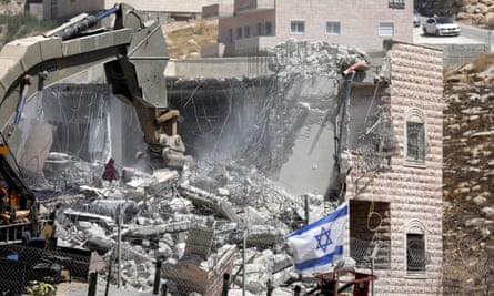 An Israeli army excavator demolishes a building in the Palestinian village of Sur Baher