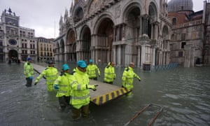 Workers install walkways amid rising water levels at St Mark's Square in Venice