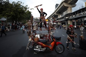 Bangkok, Thailand. An anti-government protester stands on top of a modified motorcycle as she joins a street protest calling for political and monarchical reform